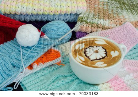 A Cup Of Latte Art On A Knitted Vest Background