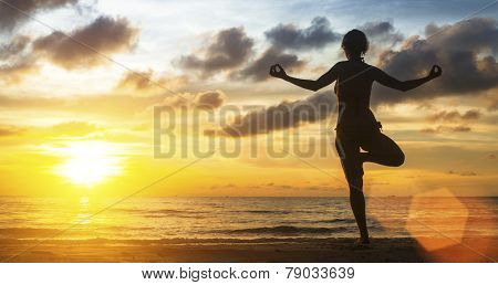Young woman yoga silhouette meditating on the ocean beach at amazing sunset.