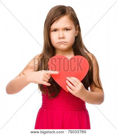 Portrait of a sad little girl holding red heart and pointing to it using index finger, isolated over white
