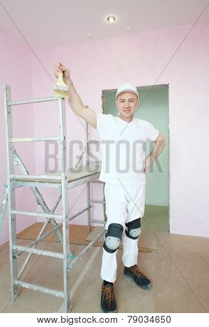 Happy plasterer in white clothes and kneepads standing near scaffolding in pink room