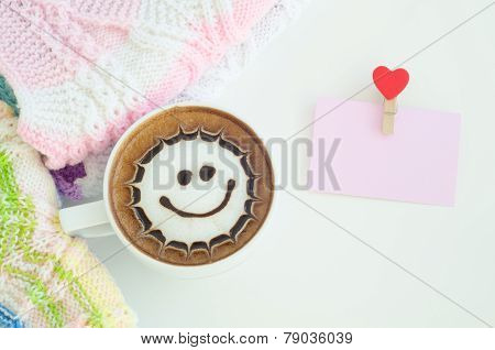 A cup of latte art and a knitted vest