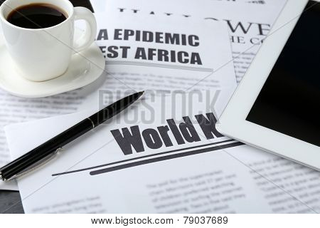 On-line news concept. Computer mouse, PC tablet, cup of coffee and newspaper, close-up