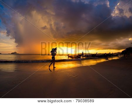 Woman on at Sunset on the beach of Ao Nang in Krabi Thailand