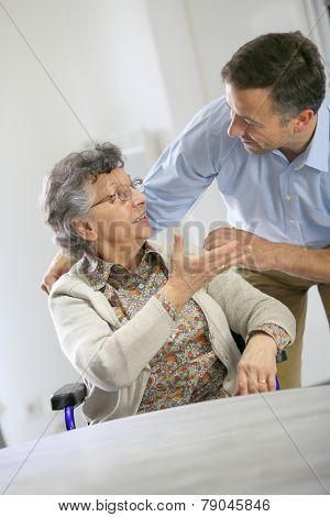 Homecarer supporting elderly woman at home