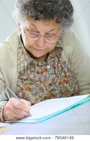 Elderly woman in wheelchair filling up medical form