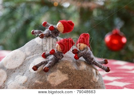 Christmas Gnomes Playing On A Stone