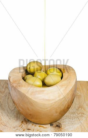 Olive Oil In Thin Trickle Flows On Olives In Bowl