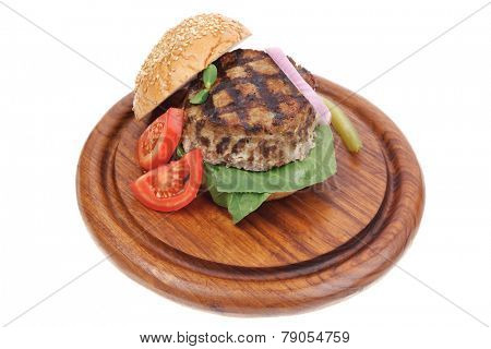 extra thick hot beef meat hamburger dinner on wooden plate with tomatoes and salad isolated on white background