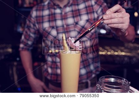 Bartender is decorating a cocktail with mango slices