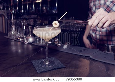Bartender is making a cocktail with leechee, toned image