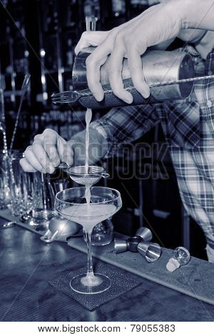 Bartender is straining drink in a glass, toned image