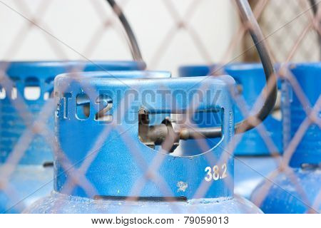 Gas Tank Behind Wire Fence Focusing At The Tank.