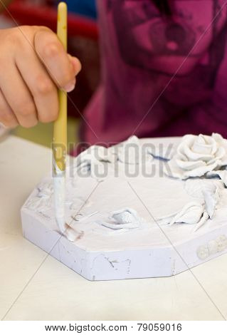 Asian Girl's Hand Painting The White Color To The Piece Of Papermache For The First Step.