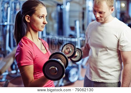 Portrait of pretty girl training with barbells in gym