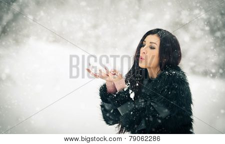 Woman blowing snow from her hands enjoying the winter. Happy brunette girl playing with snow