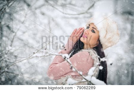 Woman with white fur cap smiling enjoying the winter scenery in forest. Side view of happy brunette