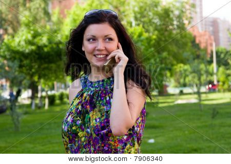 Woman Is Talking Mobile Phone Outdoors.