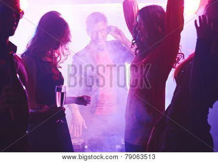 Deejay looking at dancing girl at party