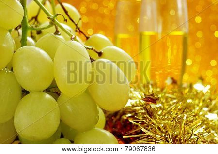 closeup of a bunch of grapes and glasses with champagne in the background for the traditional celebration of the New Year in Spain