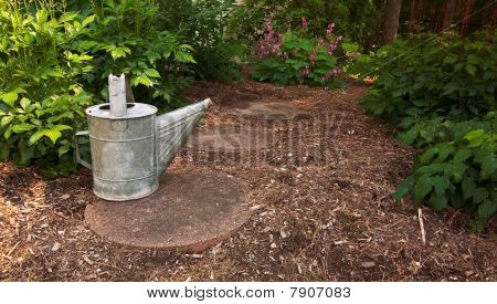 An Old Watering Can Sits On A Garden Path