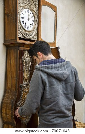 Young Man Winding The Mechanism On A Clock