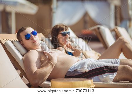 A young couple in love sunbathing by the sea on the beach.