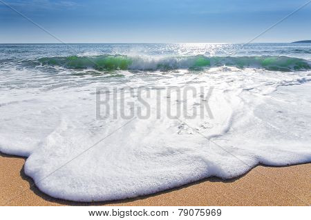sand sea beach and blue sky after sunrise and splash of seawater