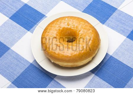 A fresh, delicious glazed donut on a classic, checkered diner tablecloth
