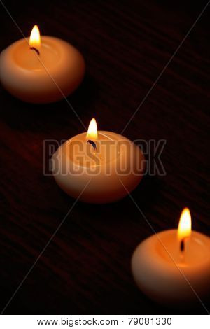 Three Candles On A Dark Wooden Table.