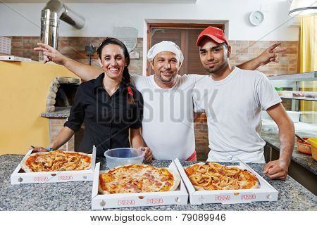 chef baker, pizza cook and waitress in uniform at pizzeria restaurant kitchen