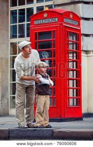 Father and son outdoors by red phone booth