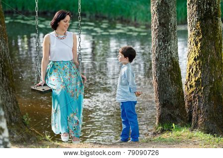 Mouther and cute little boy on swing in playground
