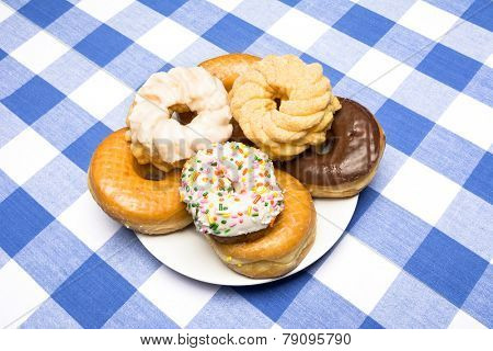 A plate of delicious, fresh donuts on a classic diner checkered blue and white tablecloth