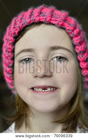 Little girl smiling portrait missing front tooth with winter hat