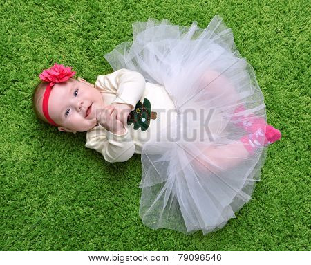 New Born Infant Child Baby Girl Lying Happy Smiling On Green Grass Blanket