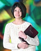 foto of tween  - A pretty young tween happily carrying her Bible before a large - JPG