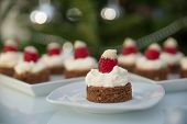 stock photo of brownie  - Santa hat brownie bites with chocolate brownie and raspberries - JPG