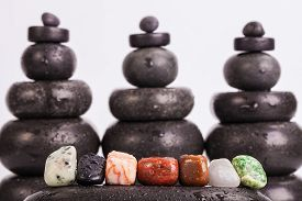 pic of lapis lazuli  - Row of seven chakra colored crystals lined in a row on wet smooth polished hot massage black stone with a blurred backgrounds from hot massage black stones - JPG