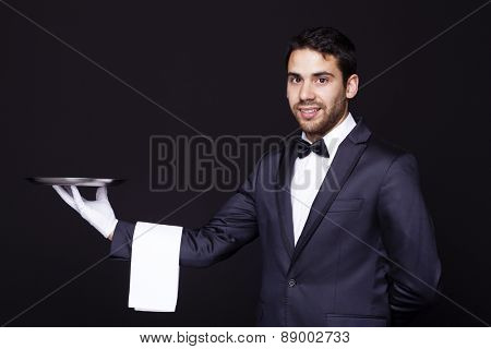 Portrait of a smiling waiter holding an empty silver tray against dark background