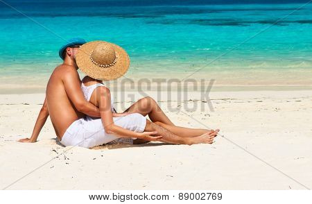 Couple in white relax on a tropical beach at Maldives