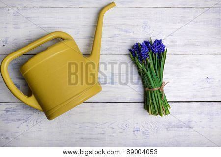 Flowers Bouquet With Watering Can On Wooden Table. Top View