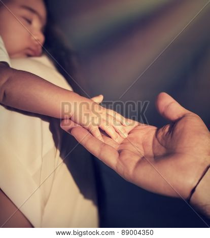 Closeup photo of cute little baby on mothers hands touching fathers hand, bright sun rays shining as a blessing of God, hope and protection concept