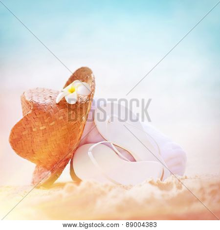 Summer holidays background, closeup photo of stylish beach clothing on sandy seashore, nice straw hat white flip flops, necessary accessories for summer vacation on beach resort