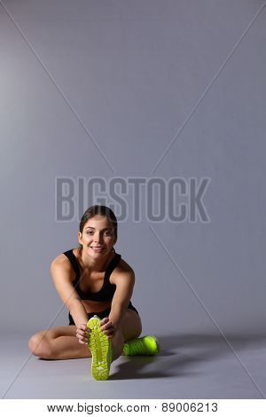 Woman sitting with crossed legs on the floor.