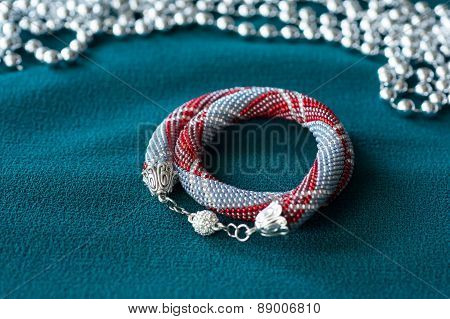 Necklace From Small Beads On A Green Textile Background