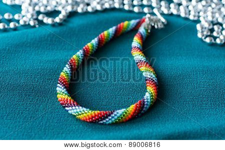 Multi-colored Necklace On A Green Textile Background