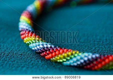 Fragment Of A Multi-colored Necklace On A Textile Background