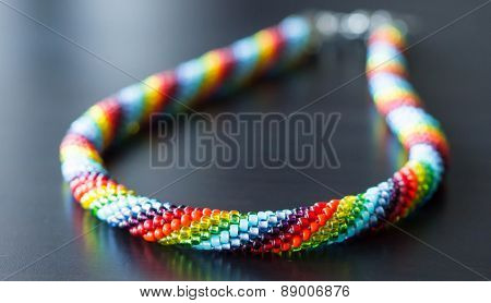 Necklace From Multi-colored Beads On A Dark Wooden Background
