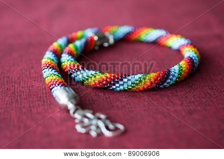 Necklace From Multi-colored Beads On A Red Textile Background