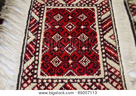 Rug handmade with black pattern on red background